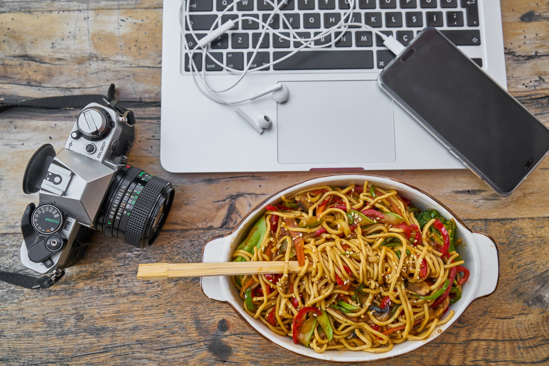 pasta on bowl beside dslr camera and laptop computer